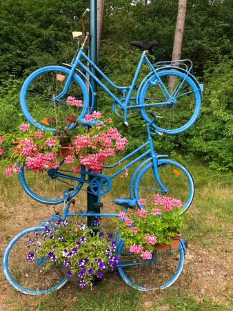 Three blue bicycles on top of each other as art