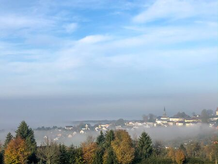 View of the Schoneck town in the Vogtland in Saxony with blue sky. Fog read on the city.