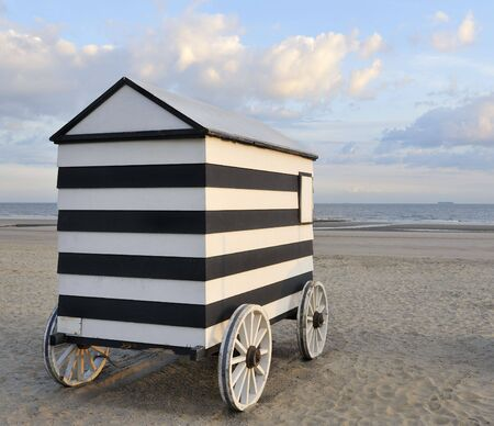 Old wheeled bathing hut on empty sandy beach with sea behind photo