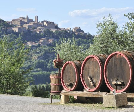 montepulciano: wine barrels and wine-making equipment with the town of Montepulciano in background, Italy Stock Photo