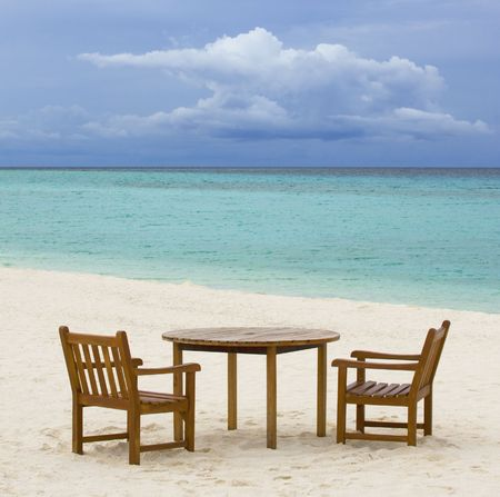 Table and chairs on empty white sand beach photo