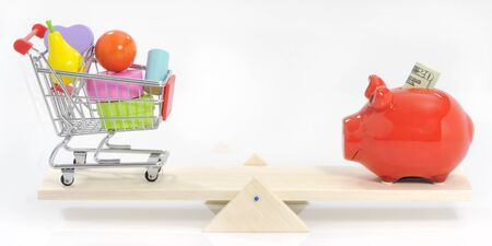 see saw: Saving and balanced spending concept savings pig and shopping cart on see-saw