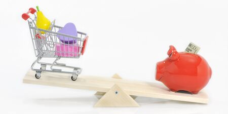 Saving and under-spending concept savings pig and shopping cart on see-saw Stock Photo - 11532147
