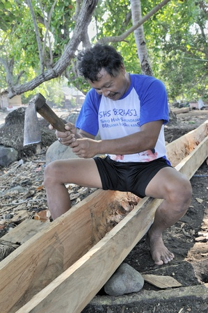 keel: Man with axe carving out the keel on a indonesian fishing boat