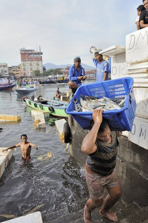 sulawesi: Young men unloading fish from boats at the market in Manado, Sulawesi, indonesia