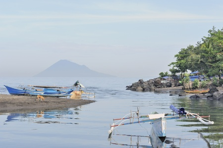 pulau: Outrigger boats in sandy harbor with conical volcano Pulau Manado Tua behind. Manado, North Sulawesi, Indonesia Stock Photo