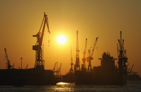 drydock: Ship in dry-dock and cranes at sunset, Hamburg, Germany