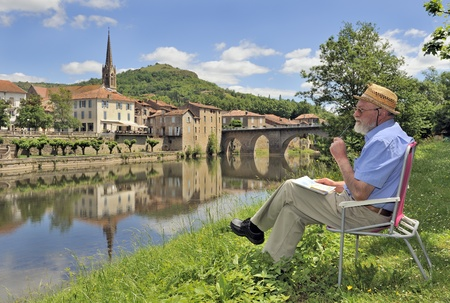 man painting: Retired man painting by bank of river in rural france.   saint-antonin-noble-val, midi-pyrenees, southern france