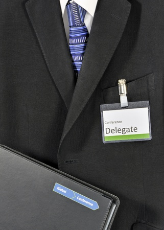 Closeup on male business suit with conference folder and delegate badge. The conference logo has been falsified Stock Photo