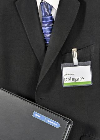 delegar: Primer en traje masculino con la carpeta de conferencias y credencial de delegado. El logo de la conferencia ha sido falsificada
