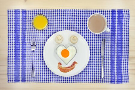 bacon love: English style breakfast with love-shaped egg and bacon face Stock Photo