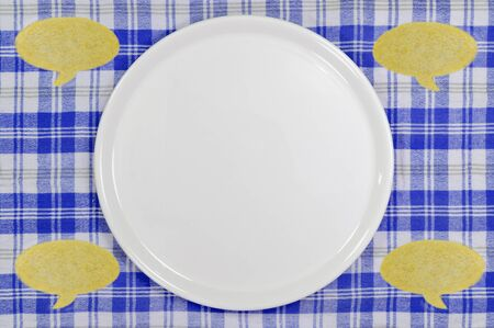 commentary: food concept with copyspace, empty white plate and speech bubbles made from cookie dough on blue checked tablecloth