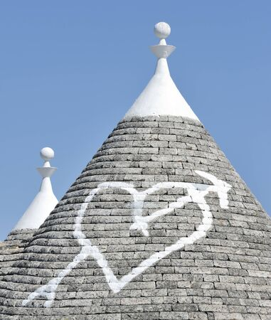trulli: Love heart painted on traditional trulli rooftop at Alberobello, Puglia, Italy Stock Photo