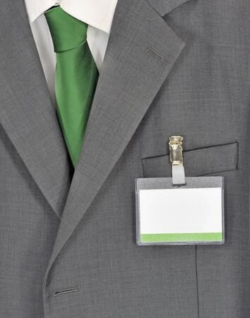 delegate: Closeup on male gray business suit, green tie and name badge