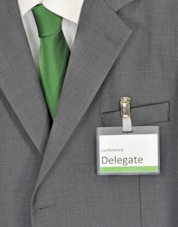 delegar: Primer en traje de hombre de negocios gris, corbata verde y la insignia de delegado de la conferencia