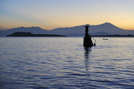 stratovolcano: Hindu sea temple in batu leong, lombok, indonesia at dawn with conical volcano rinjani behind Stock Photo