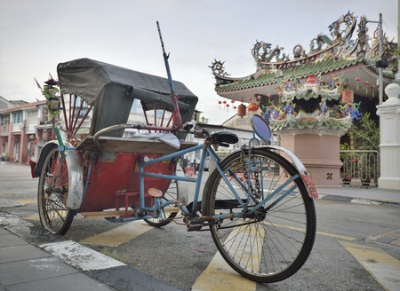georgetown: Traditional rickshaw and chinese temple in Penang street
