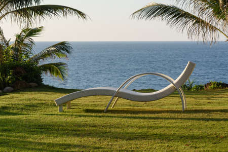Chaise longue standing on the grass against the sea