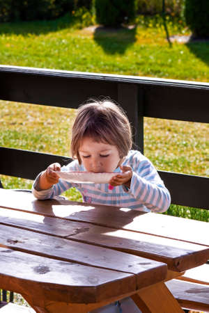Little girl  lapping her milk soup directly from plate , outdoors  photo