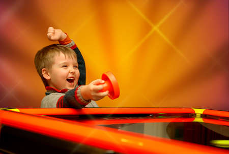 A child who has won his air hockey game, with a red mallet in his hand