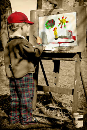 Boy painting his colorful world, outdoors  photo