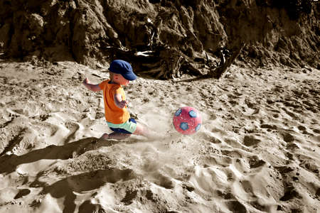 Boy playing soccer on the beach  photo