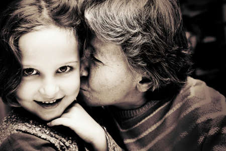 Portrait of Grandmother kissing her granddaughter  Reklamní fotografie