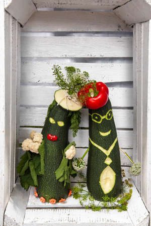 A funny pair of vegetables in love in white wooden box.