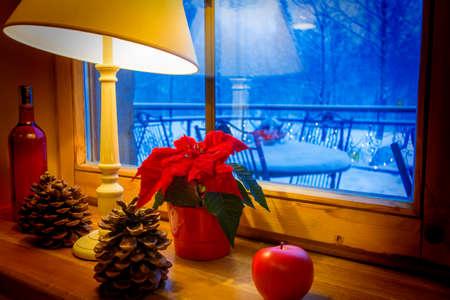 窓から見える冬景色の窓辺で温かみのあるランプとクリスマスの装飾。