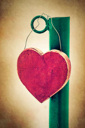 road side: Wooden heart shaped sign, hanging on the road side post.