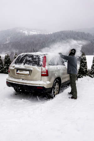 removing: Man removing snow from his car during a snow storm in mountains.