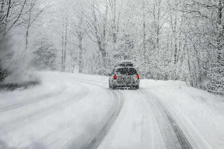車のフロント ガラスを通して撮影した冬の雪の中に運転は blured 雪で覆われています。