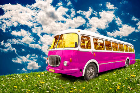 レトロなバスは、青空を背景に牧草地に駐車。 写真素材