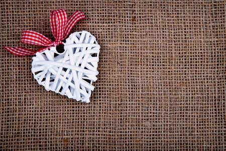 raffia: White raffia heart with red ribbon on the burlap background.