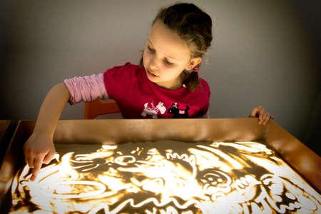 子供の女の子砂ライト テーブル上で描画します。 写真素材