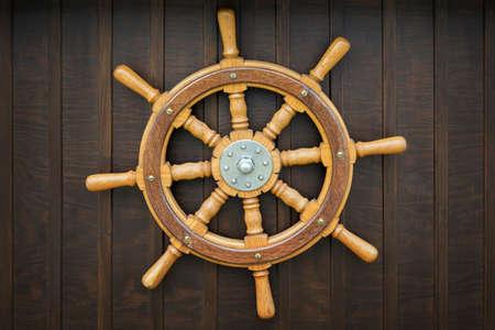 wood turning: Wooden metal old wheel steering on wood background.