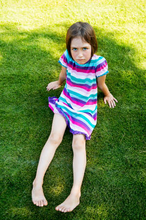 frowned: Outdoors portrait of small girl with offended look. Stock Photo