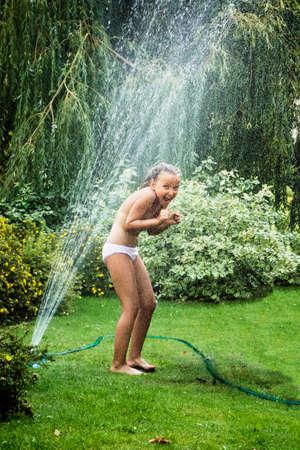 garden fountain: Young girl having fun while standing under garden fountain during hot summer day.