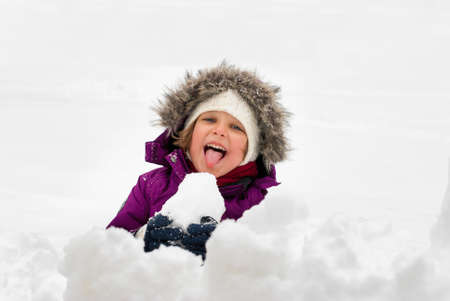 sticking out tongue: A little girl sticking out tongue while eating snow.