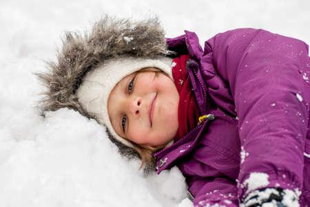 niños riendose: Niña cansada, por la que se en la nieve y sonriendo.