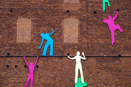 壁を登りながら助け合う人の抽象的なシルエット 写真素材