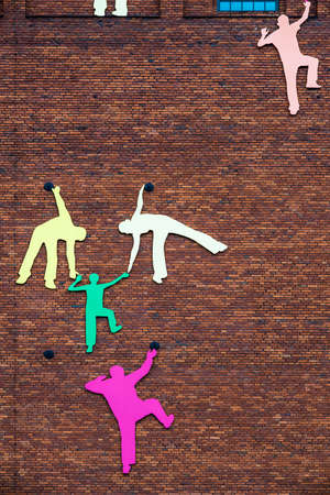 climbing wall: Abstract silhouette of people helping each other while climbing wall Stock Photo