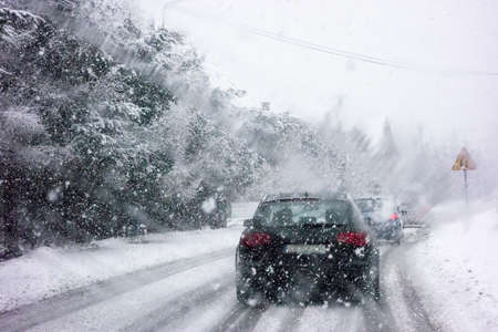 Car driving during winter snow taken through a windshield covered with blured snowflakes. Archivio Fotografico