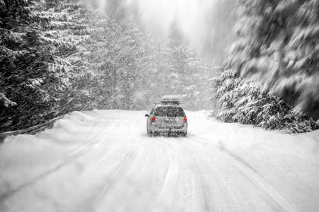 Car driving during winter snow taken through a windshield covered with blured snowflakes. Stock Photo