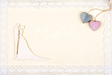 blank photo: Bride and groom silhouette on retro paper framed with lace. Two wooden hearts in corner.