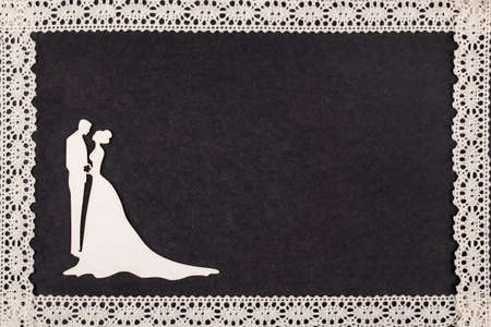 album page: Bride and groom silhouette on retro album page framed with lace.