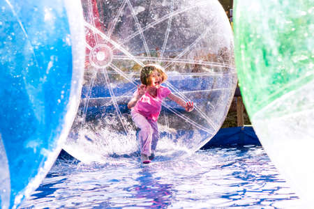 Young girl playing inside a floating water walking ball. Reklamní fotografie
