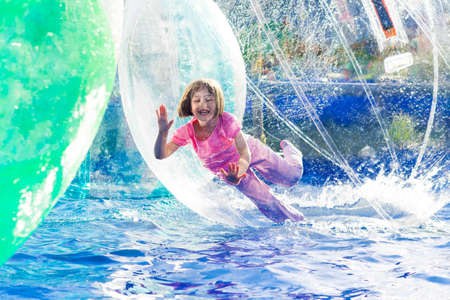 若い女の子の浮動小数点水ボールの歩行中プレーします。