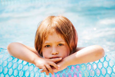 scowling: Thoughtful little girl in the pool, outdoor.