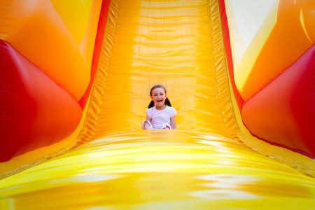 Gelukkig meisje met veel plezier op een springkasteel tijdens het glijden. Stockfoto
